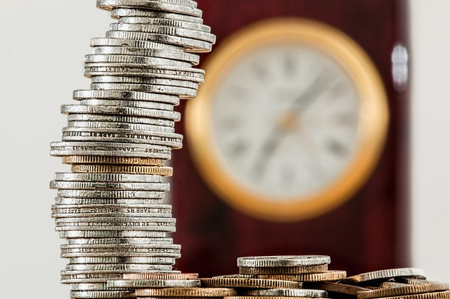 stacked-coins-in-front-of-blurred-clock